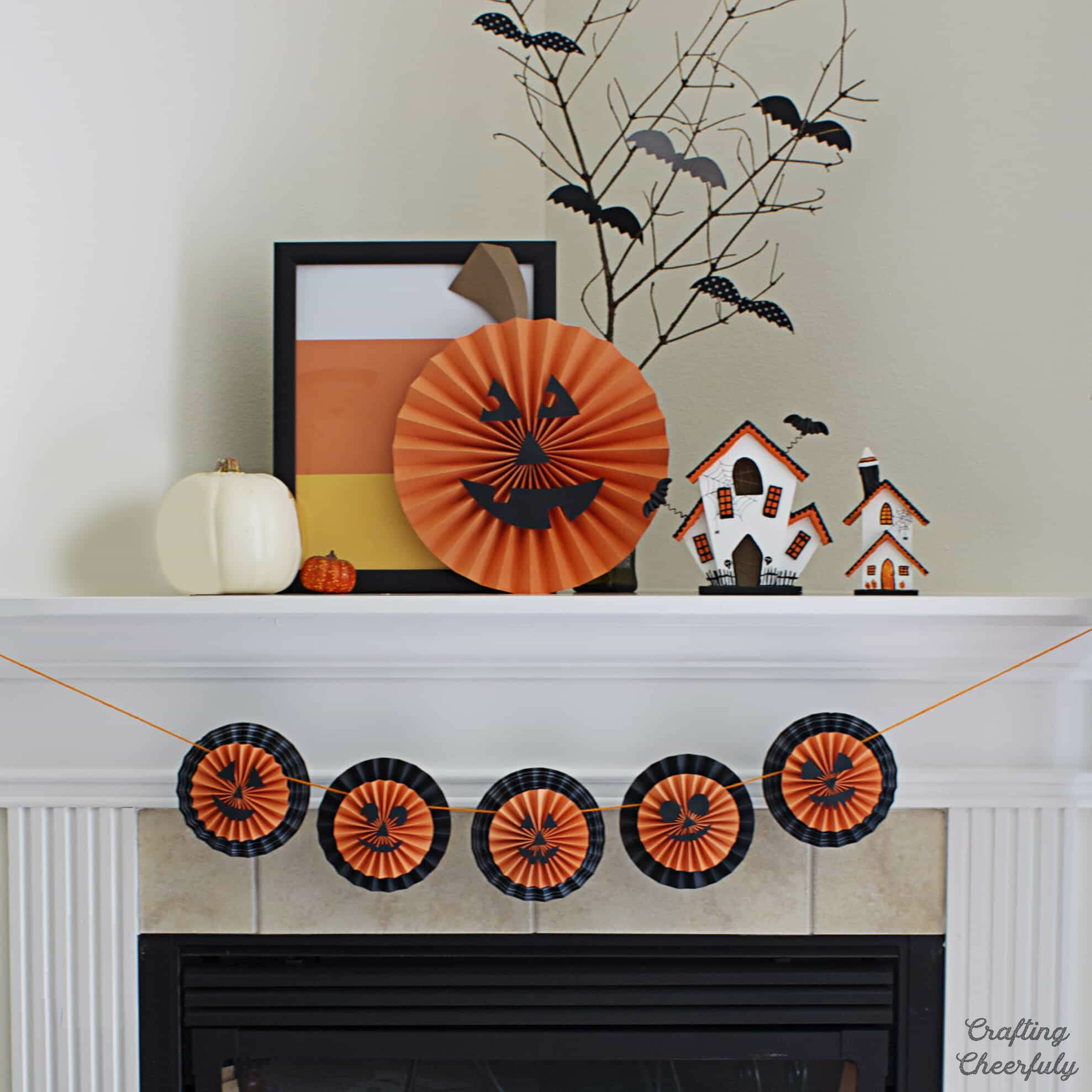 Jack-o'-Lantern Pumpkin banner hangs on a mantle with other Halloween decorations.