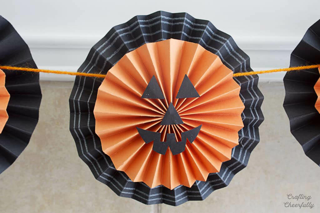 Smiling paper pumpkin made from an orange and black paper medallion.