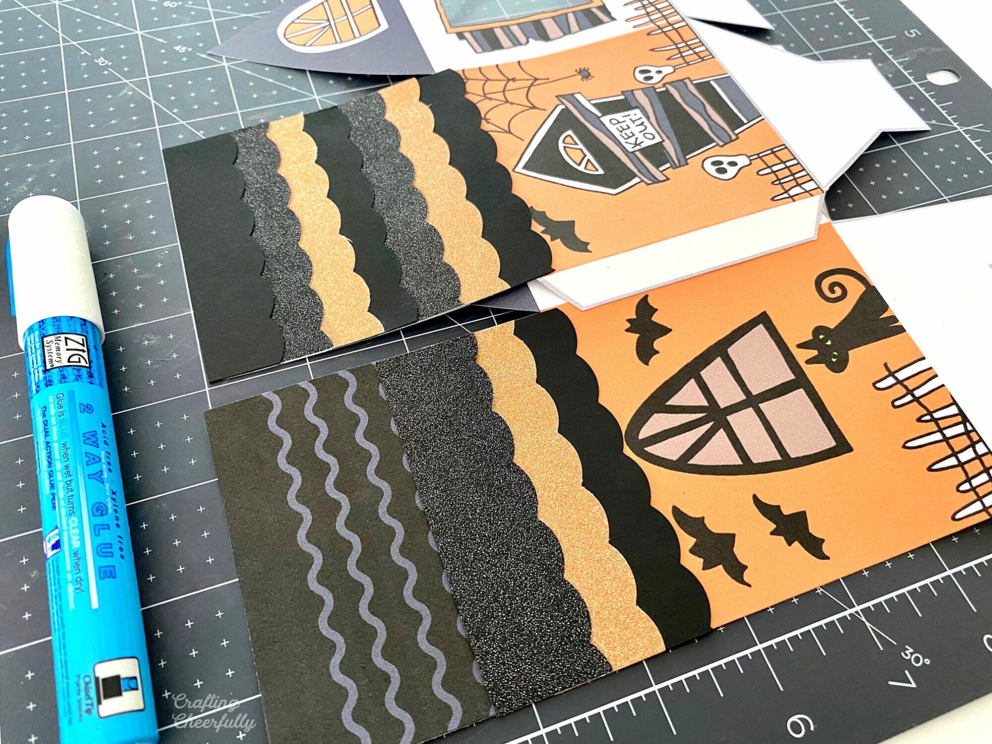 Printable boxes laying on a black cutting mat with roof pieces being added.