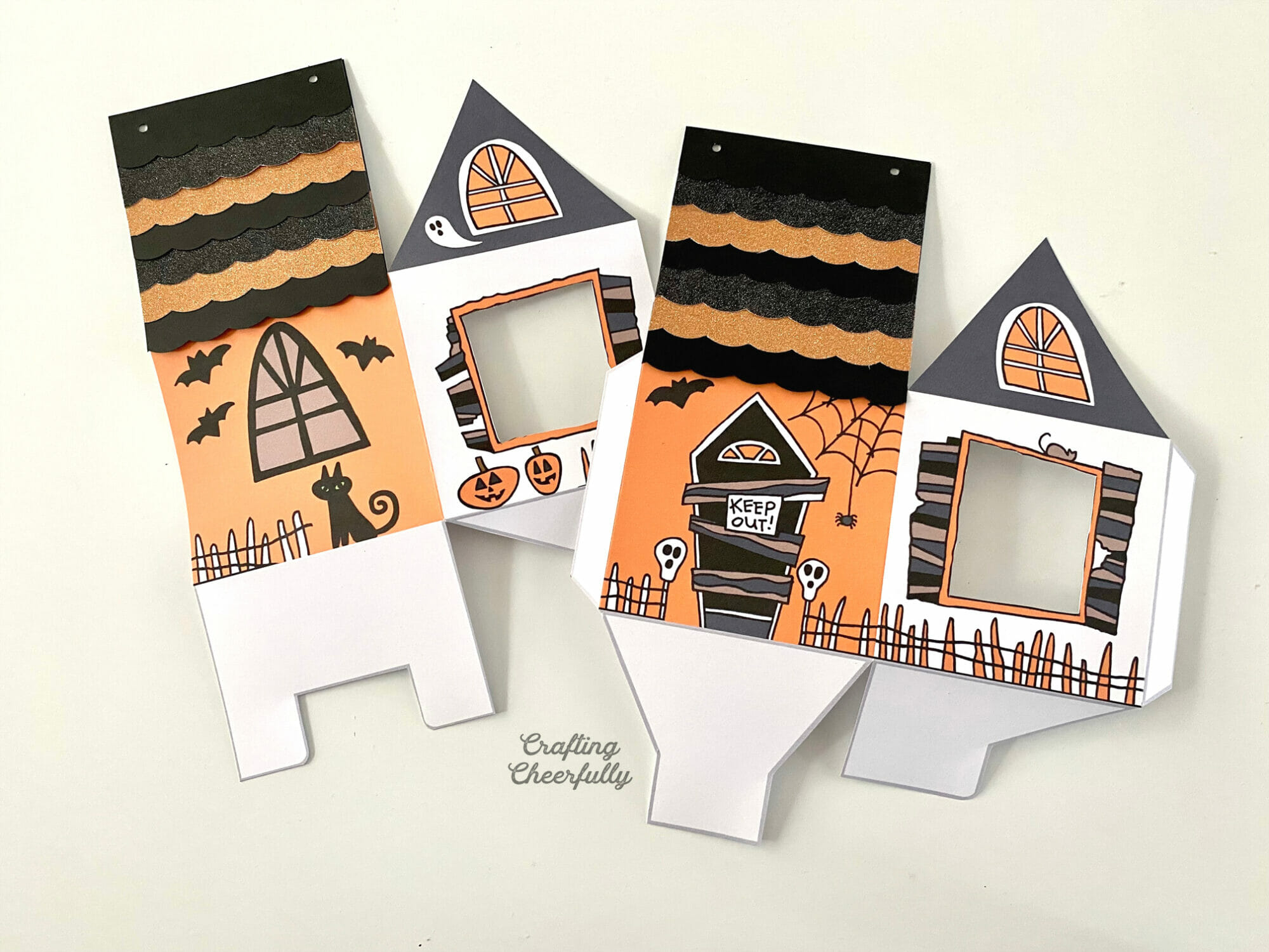 Printable haunted house boxes cut out and folded laying on table.