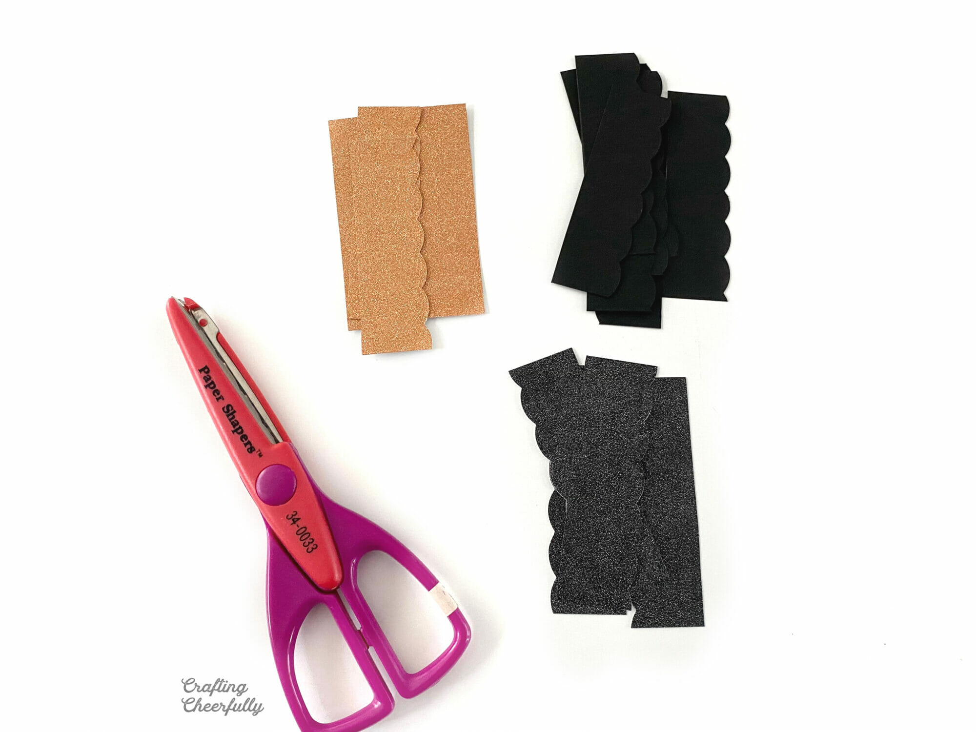 Scalloped pieces of paper in piles lay next to a decorative edge scissors.