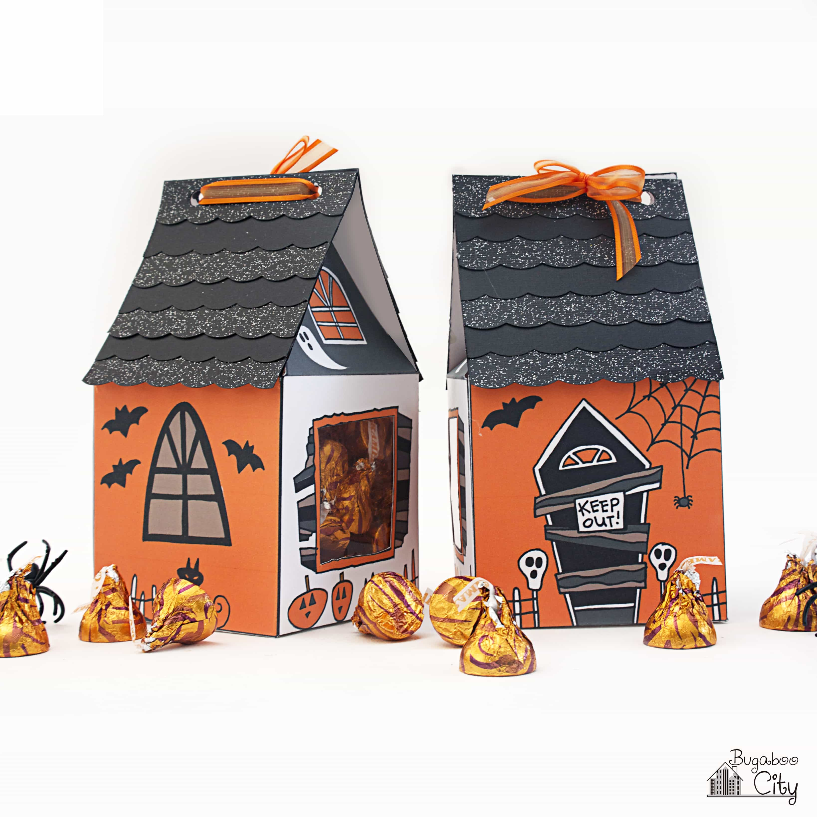 Halloween Haunted House Treat boxes with orange chocolates scattered around them.