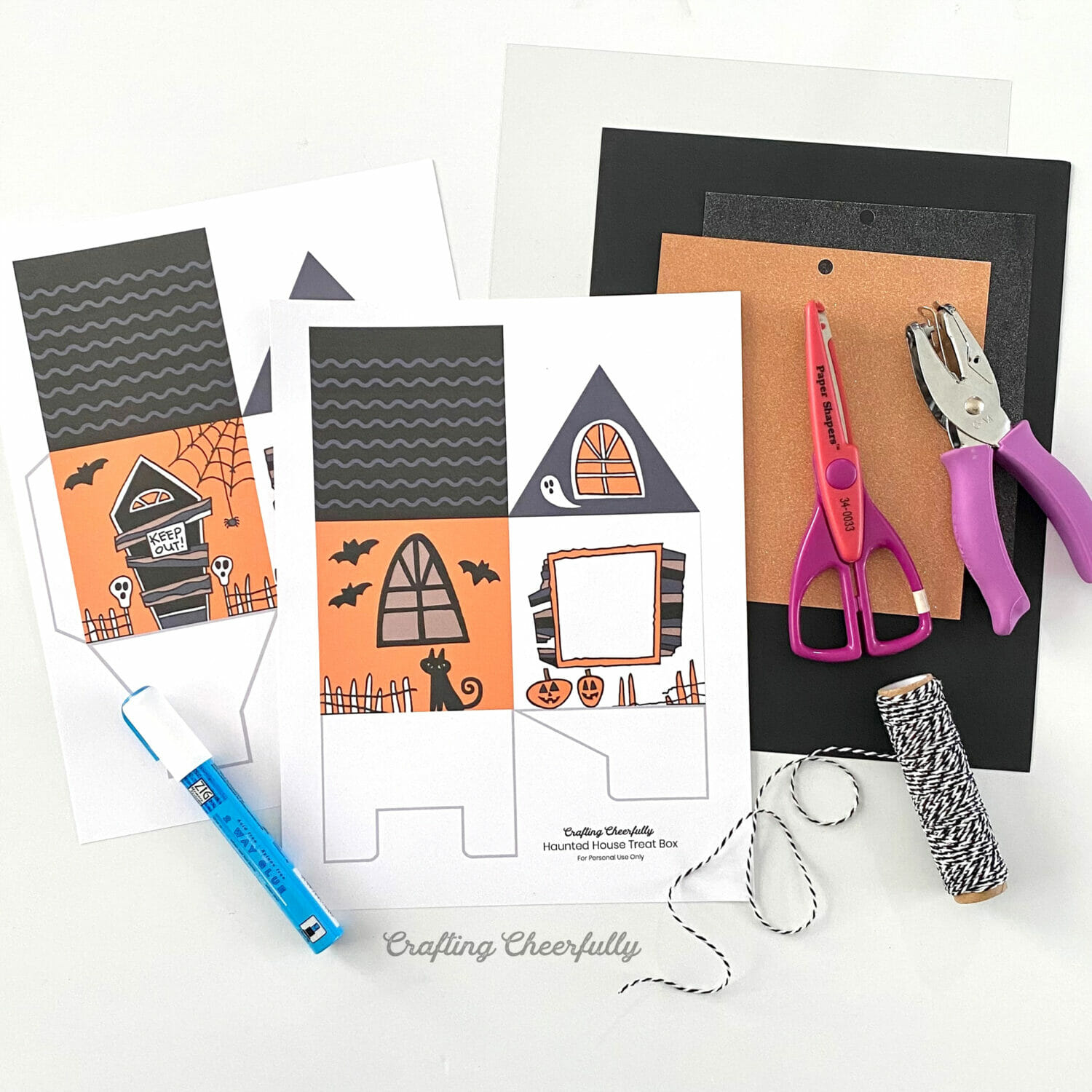Supplies needed to make a haunted house treat box lay on a white table top.