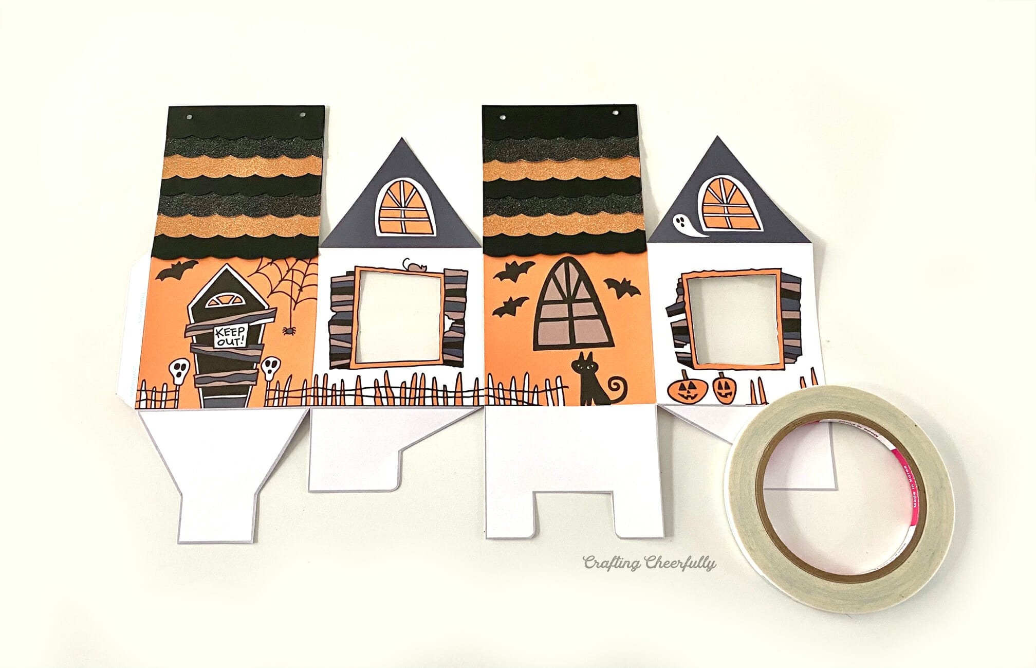Haunted House treat box laying flat next to a roll of double-sided tape.