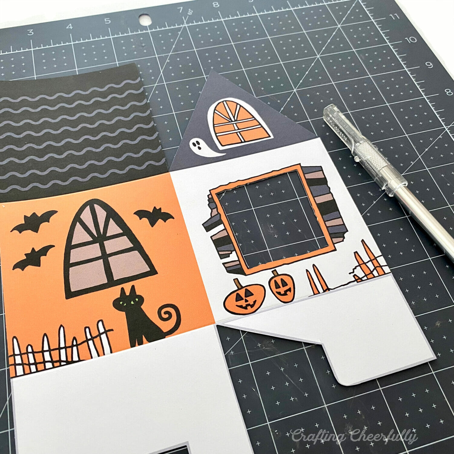Paper haunted house treat box with windows being cut out with an Xacto knife.