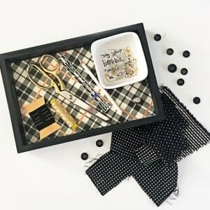 Black sewing tray filled with sewing supplies.