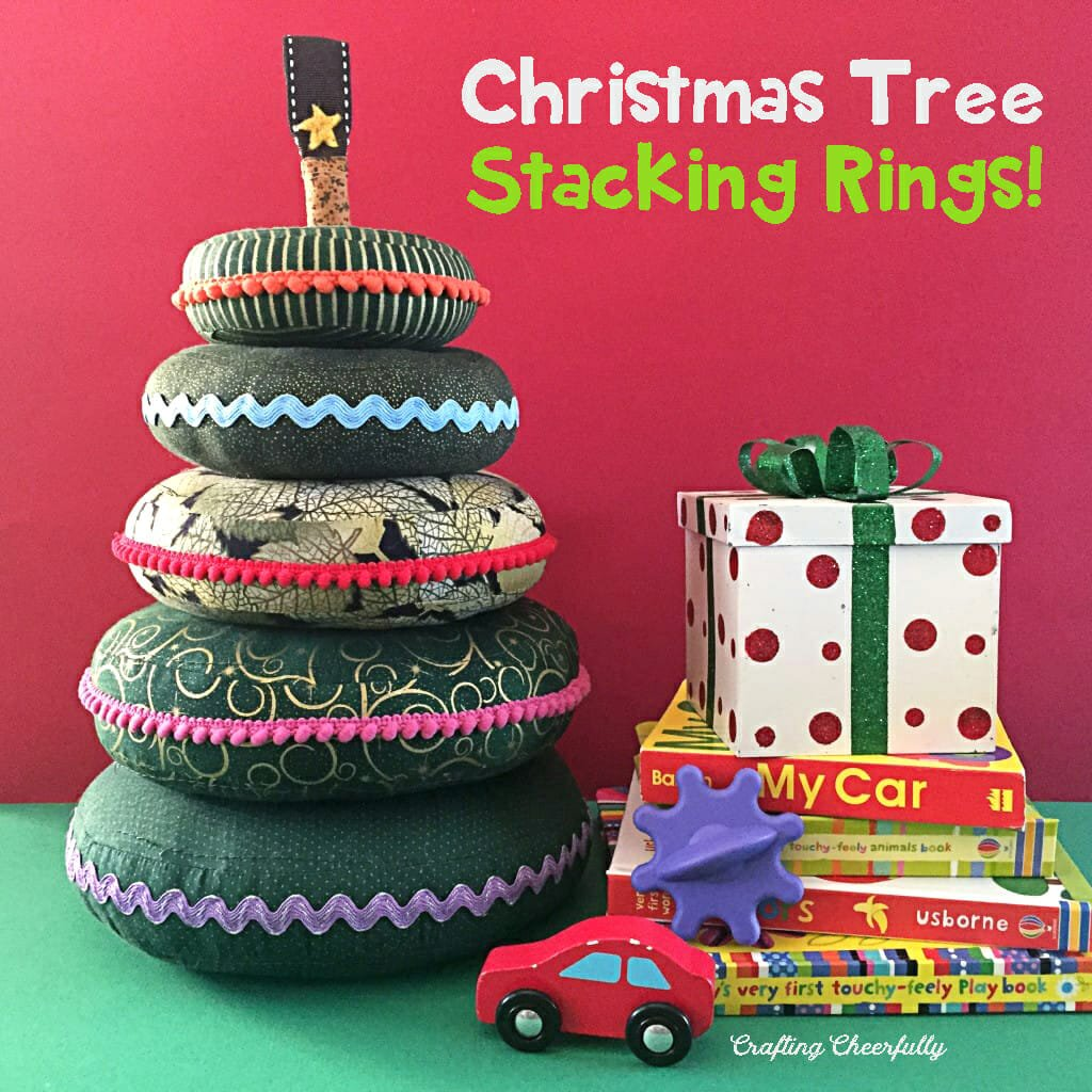 Fabric baby rings in green fabric are made to look like a Christmas tree. They sit next to a stack of books and baby toys on a green table with a red backdrop behind them.