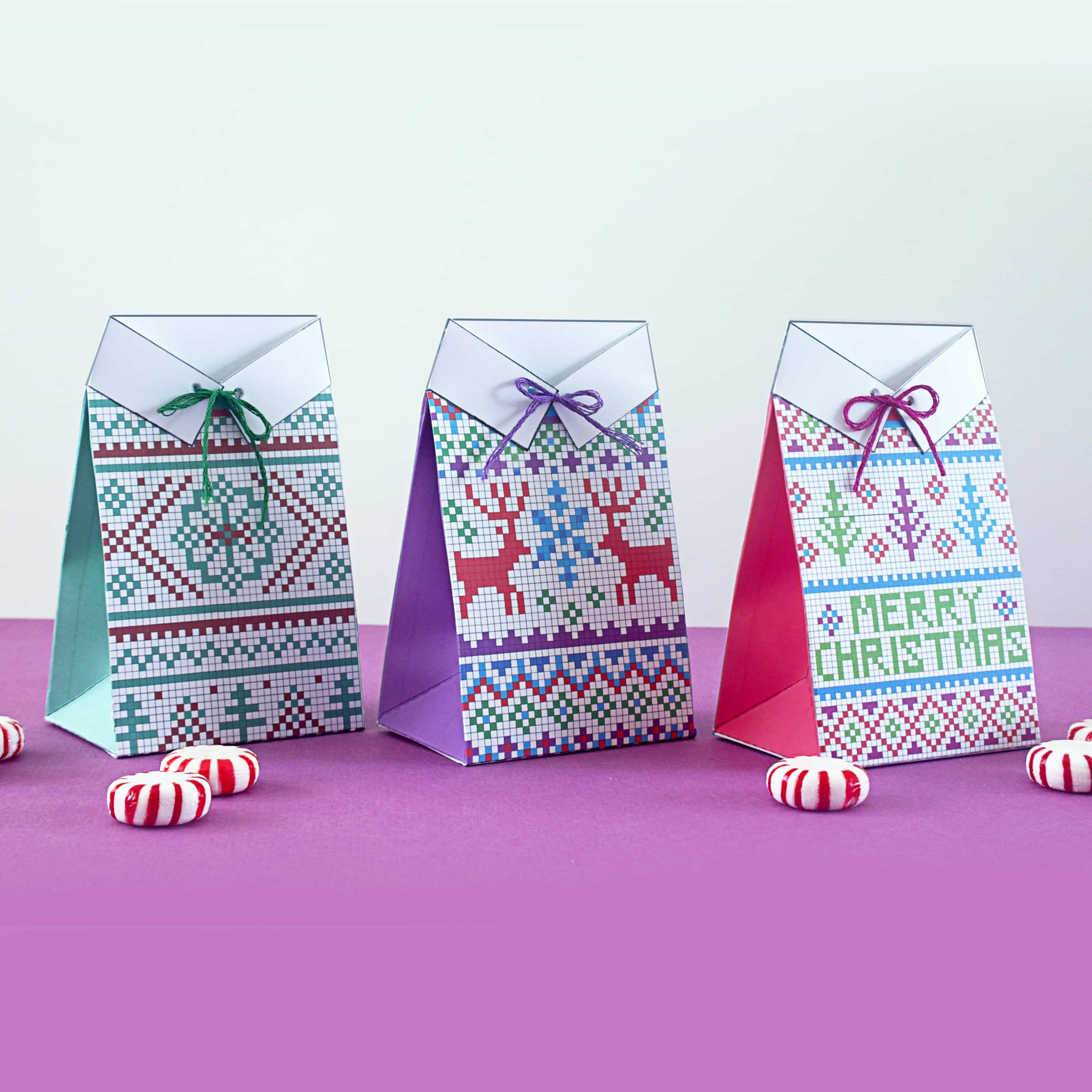 Three sweater treat boxes lined up on a purple tabletop.