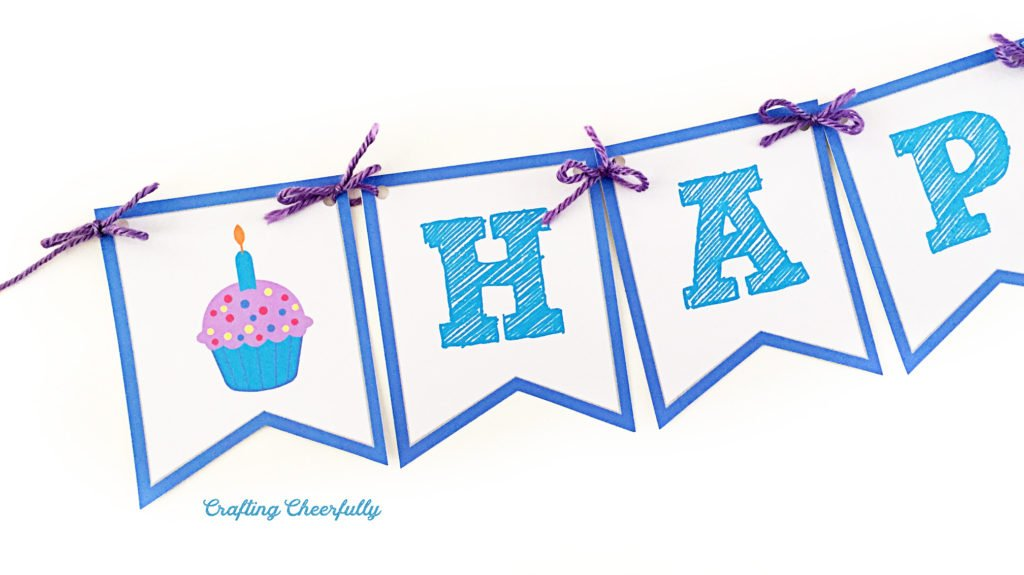 Happy Birthday banner pennants are blue and white held together with purple yarn with a cupcake on one of the pennants.