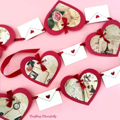 Valentine's Day banner with red hearts and white envelopes on a pink background.