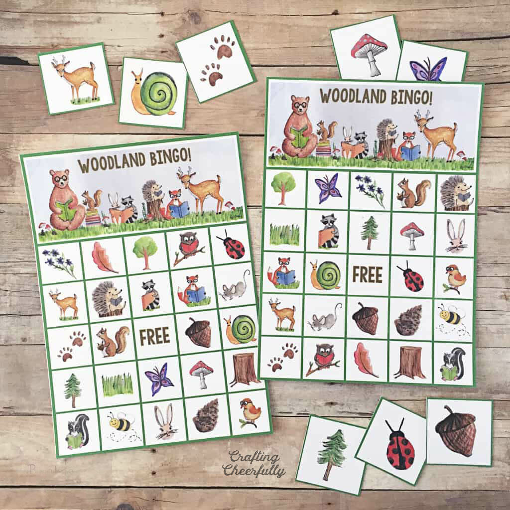 Woodland Animal BINGO printable game boards lay on a wooden table top.