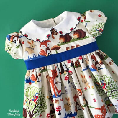 Woodland-themed baby dress laying on a green background.