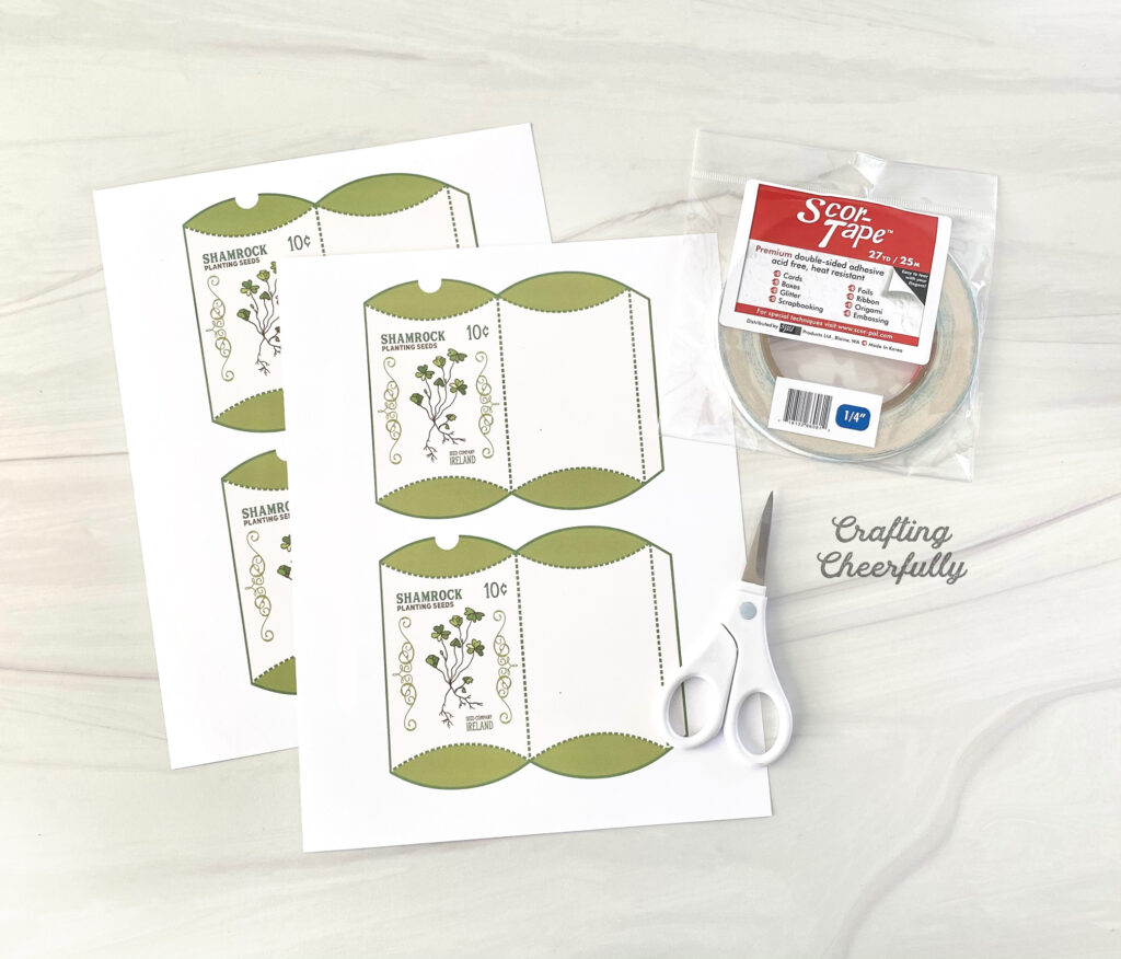 Printable Shamrock Treat Box files lay on a table with a scissors and double-sided tape.