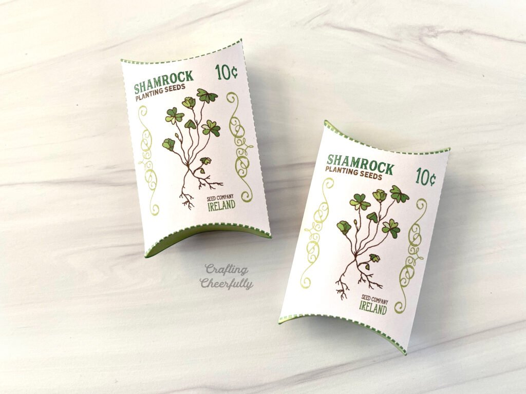 Two fully assembled St. Patrick's Day Shamrock pillow boxes lay on a table.