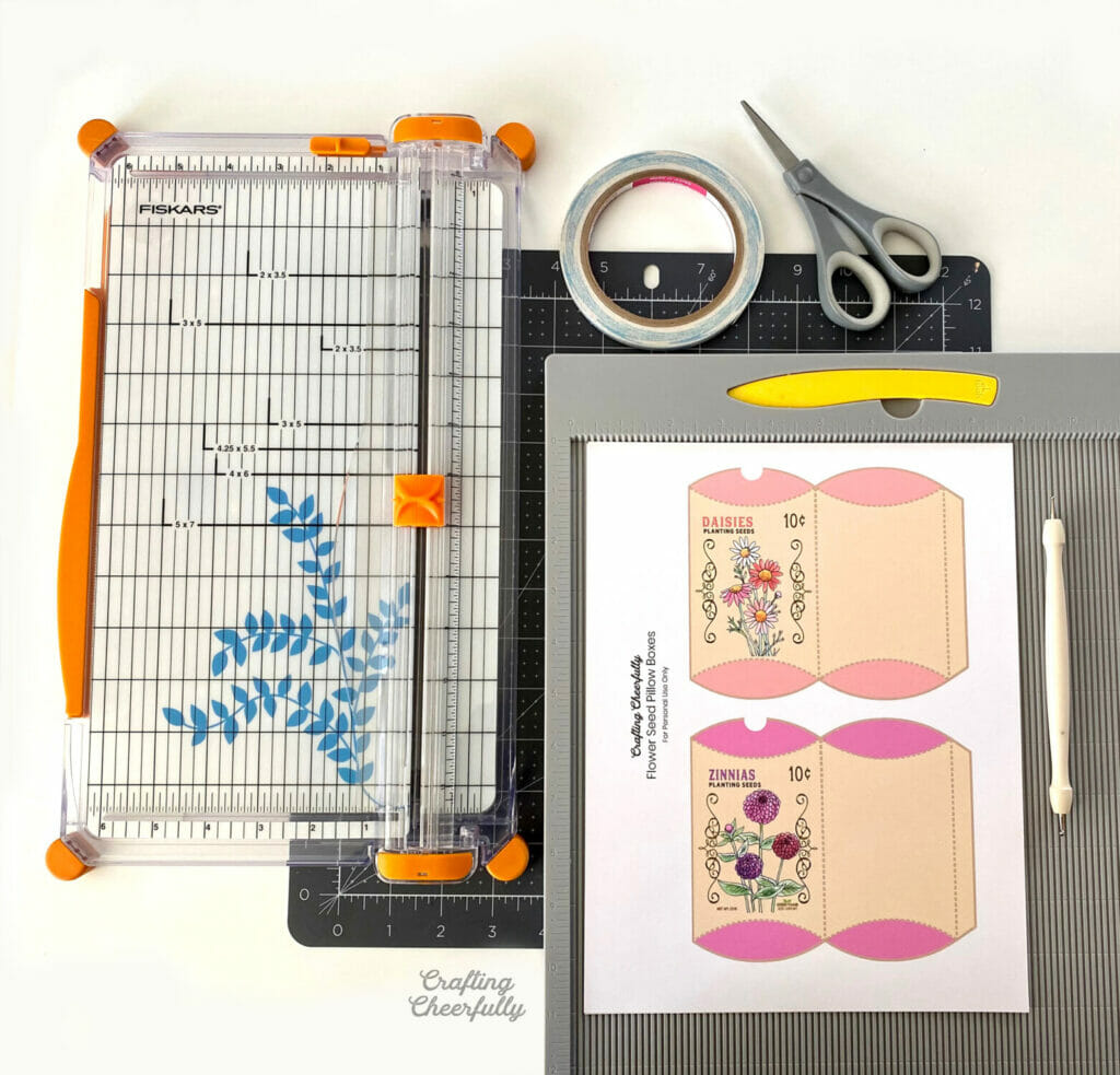 Supplies needed for flower seed treat boxes including a paper trimmer, scoring board and printables.
