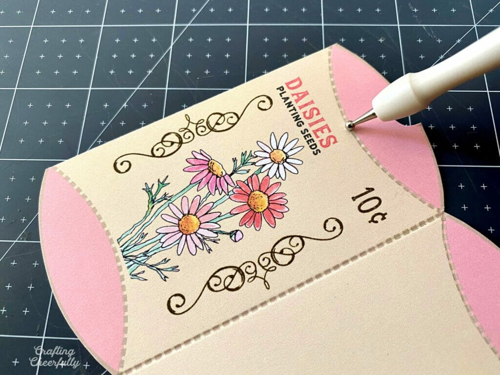 Flower seed treat box is laying on a black self-healing mat with a scoring stylus scoring along the curved edge.