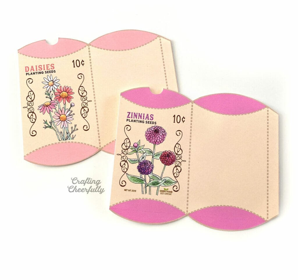 Two flower seed treat boxes unassembled laying on a white surface.