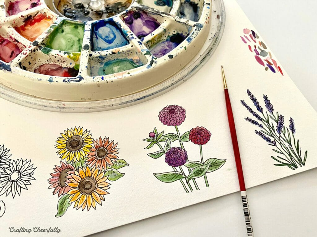 Watercolor paintings of flowers with a watercolor wheel palette and paintbrush next to them.