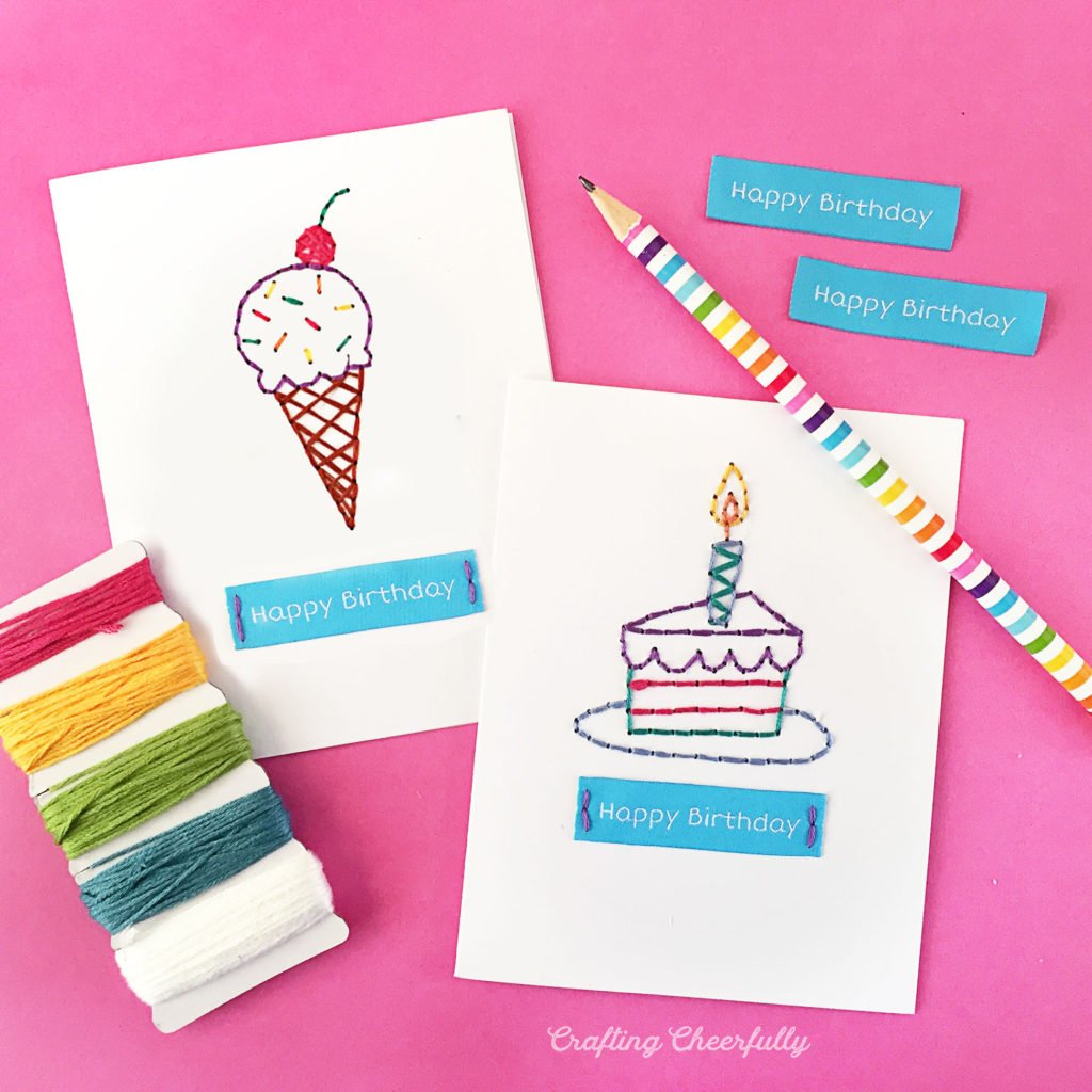 Happy Birthday embroidered cards on a pink surface with a cute pencil and embroidery threads.