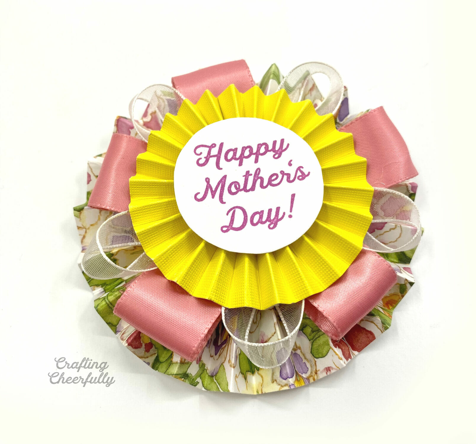 Mother's Day paper pin medallion is assembled and sitting on a white surface.