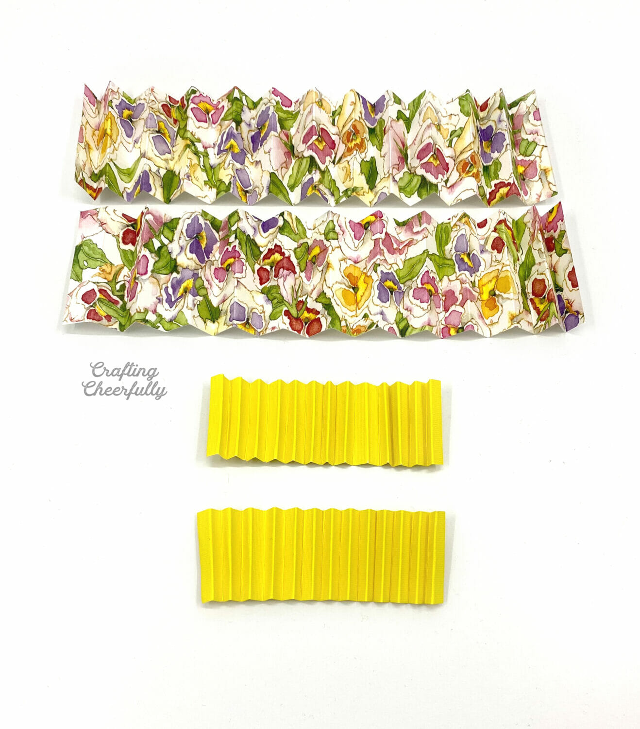 Strips of accordion folded paper lay on a table. One is larger and floral, the other is smaller and yellow.