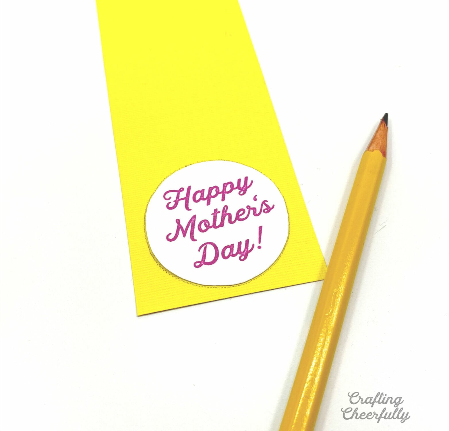A piece of yellow paper with a round label laying on it to be traced with a pencil laying next to it.