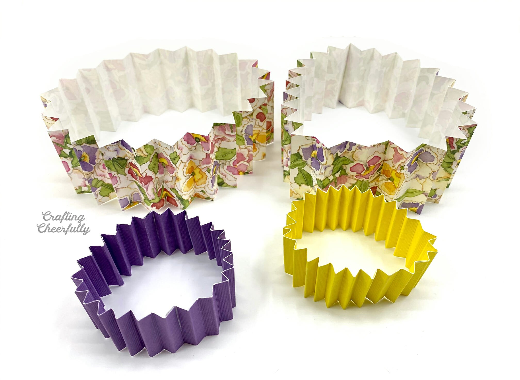 Tubes of accordion folded strips of paper lay on a white table.