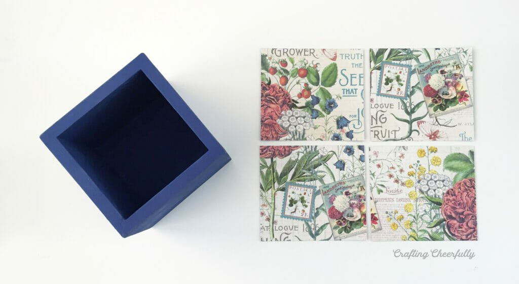 Four square of floral scapbook paper lay next to a blue wooden box.