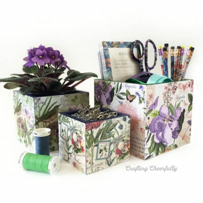 Three floral decoupage boxes filled with flowers, office supplies and safety pins.