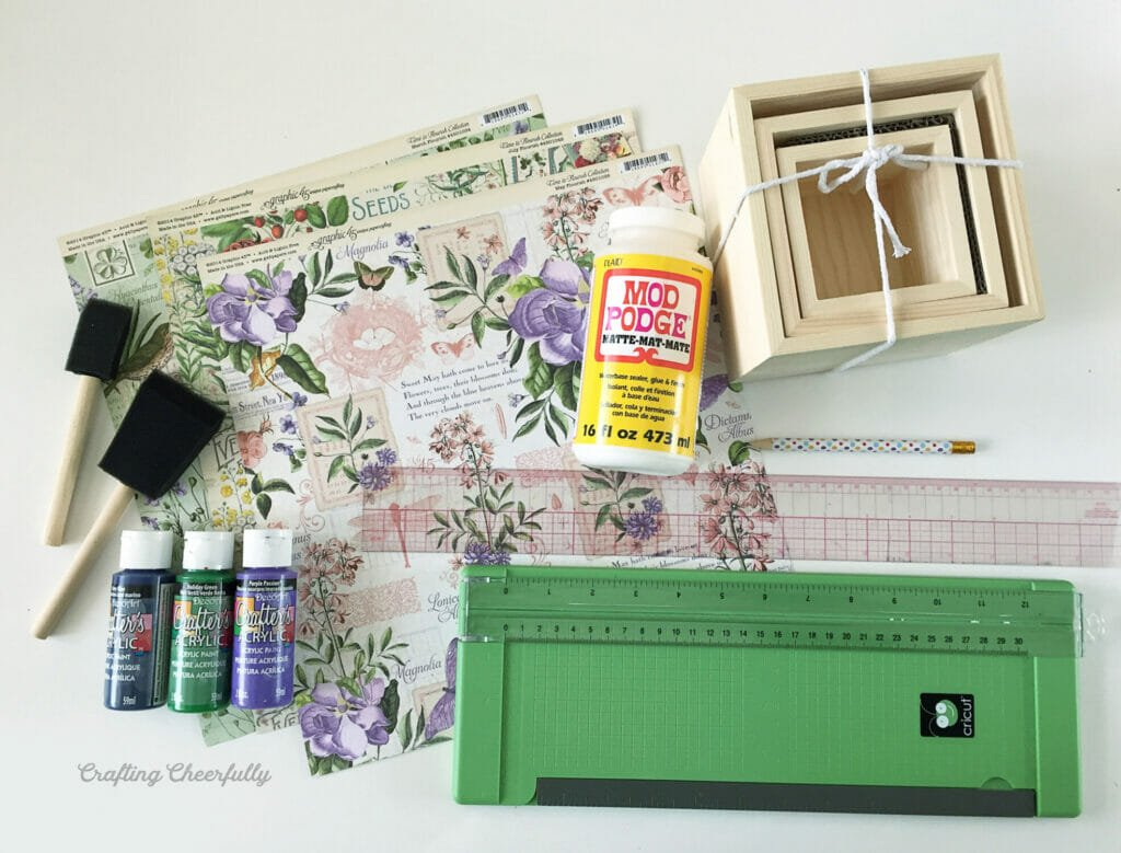 Supplies needed to make floral decoupage boxes are gathered on a white table including scrapbook paper, paint, a paper trimmer and wooden boxes.