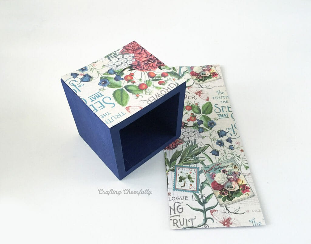 A blue wooden box with one side covered with floral scrapbook paper sits on a white surface.