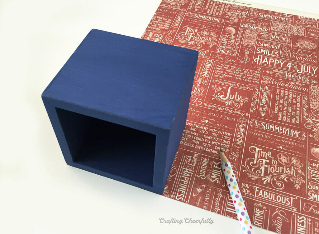 A blue wooden box lays on top of a piece of scrapbook paper with a pencil nearby.