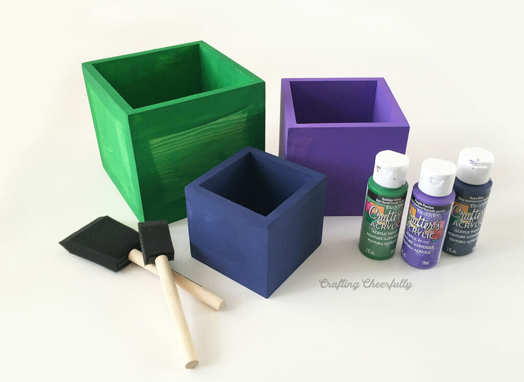 Three wooden boxes painted blue, green and purple sit next to bottles of paint and foam brushes.