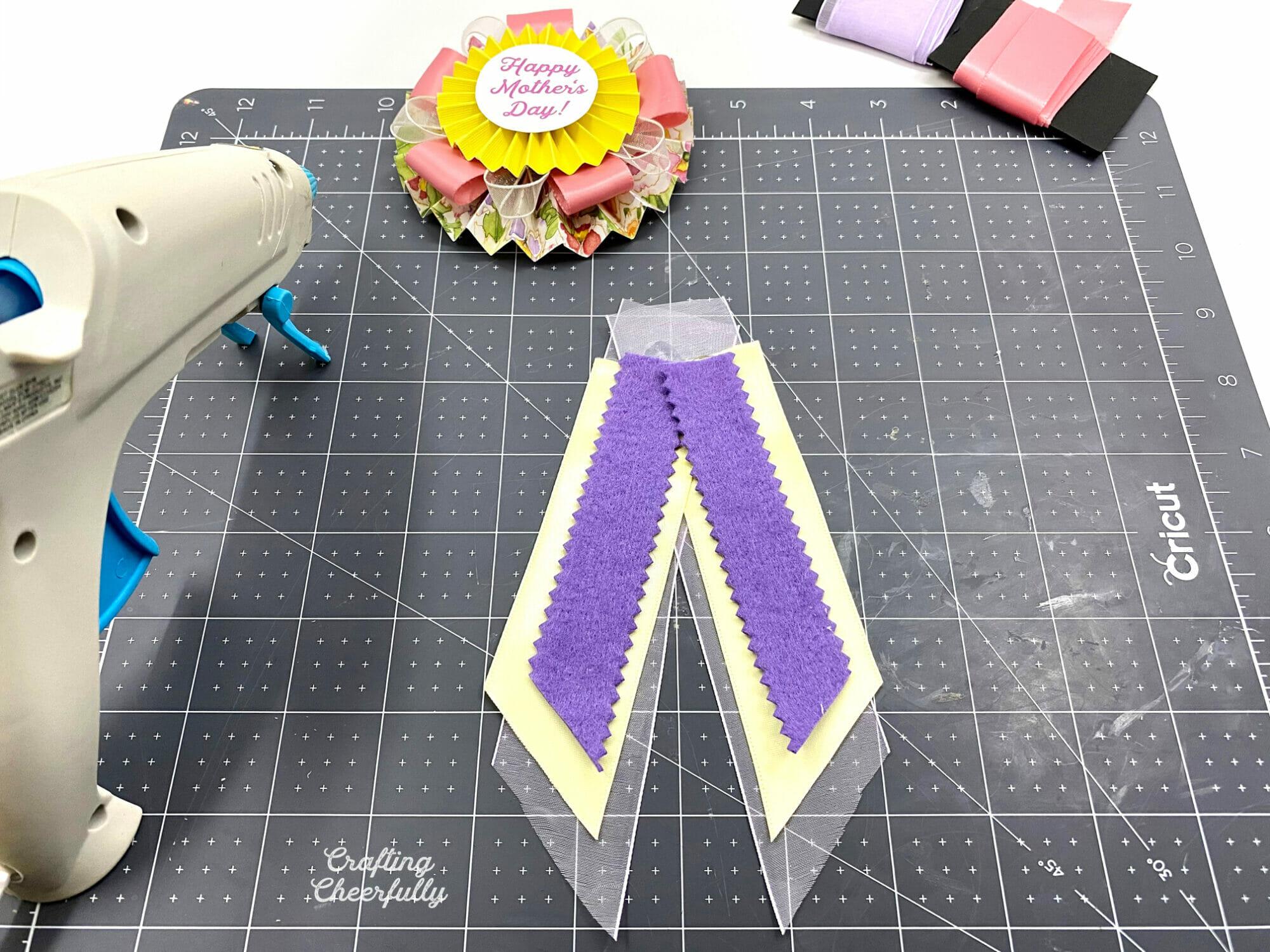 Ribbon lays on a black self-healing cutting mat with a glue gun.