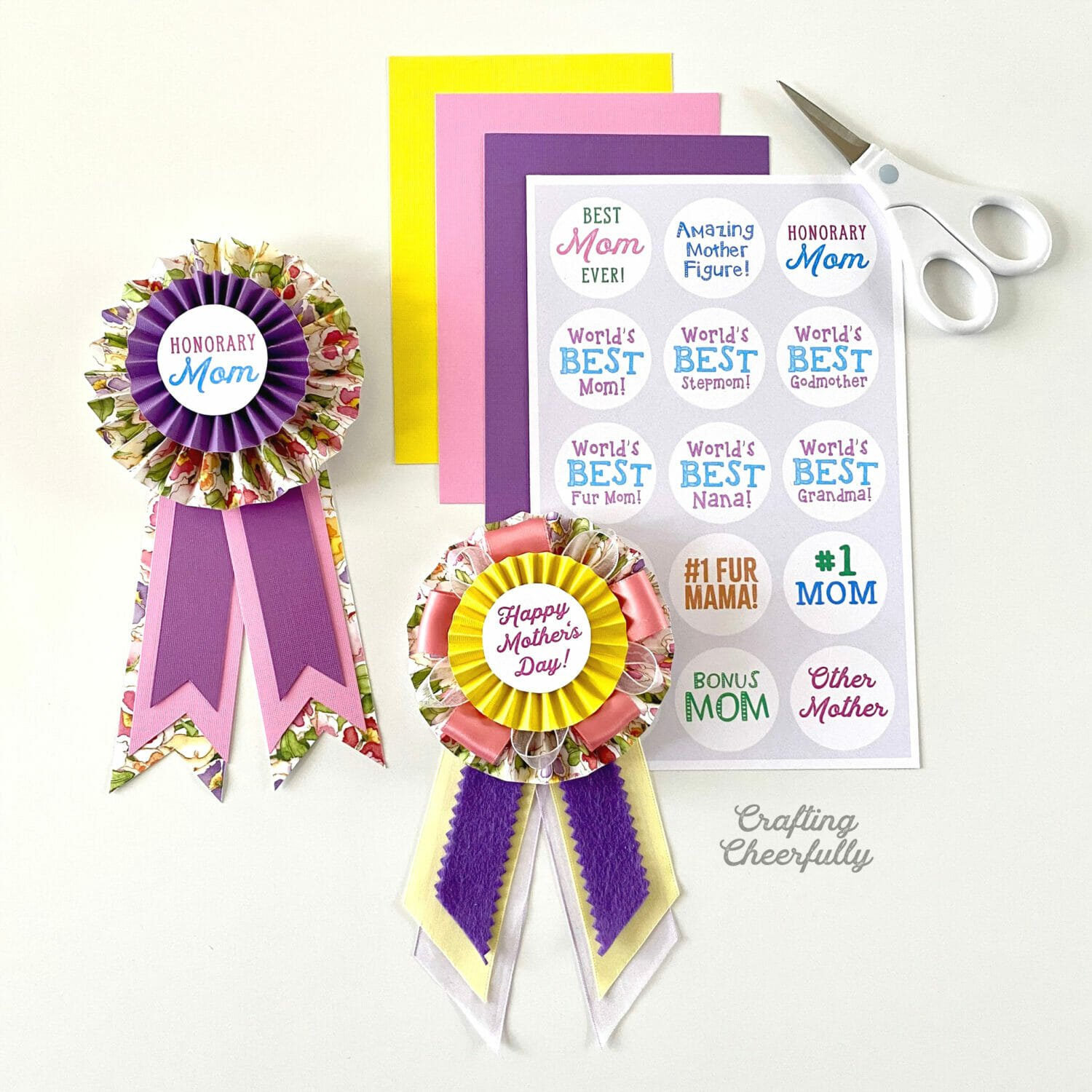 Paper medallion pins lay next to colored paper and a sheet of titles and a white scissors.