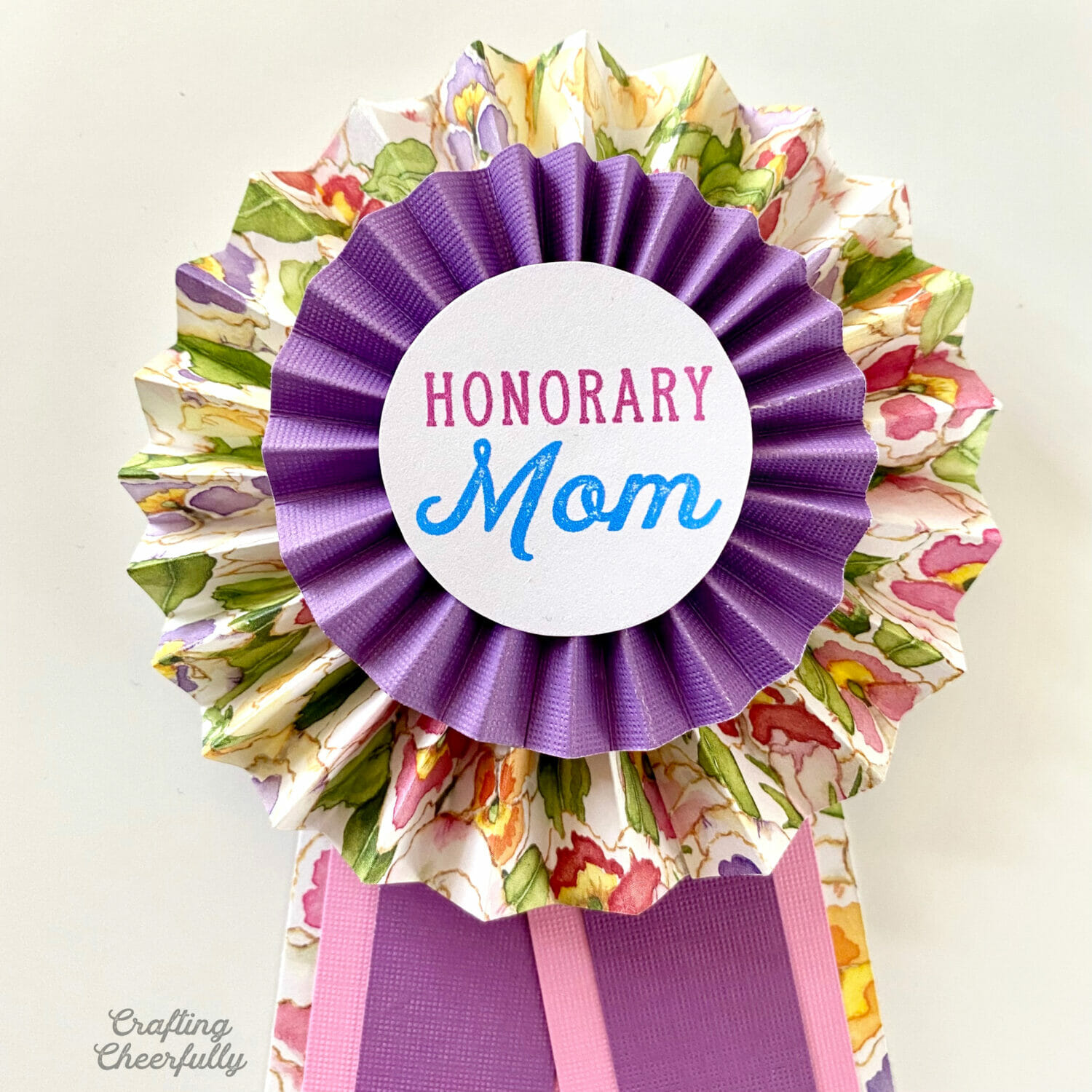 """Paper medallion pin with the words """"Honorary Mom"""" written on it."""