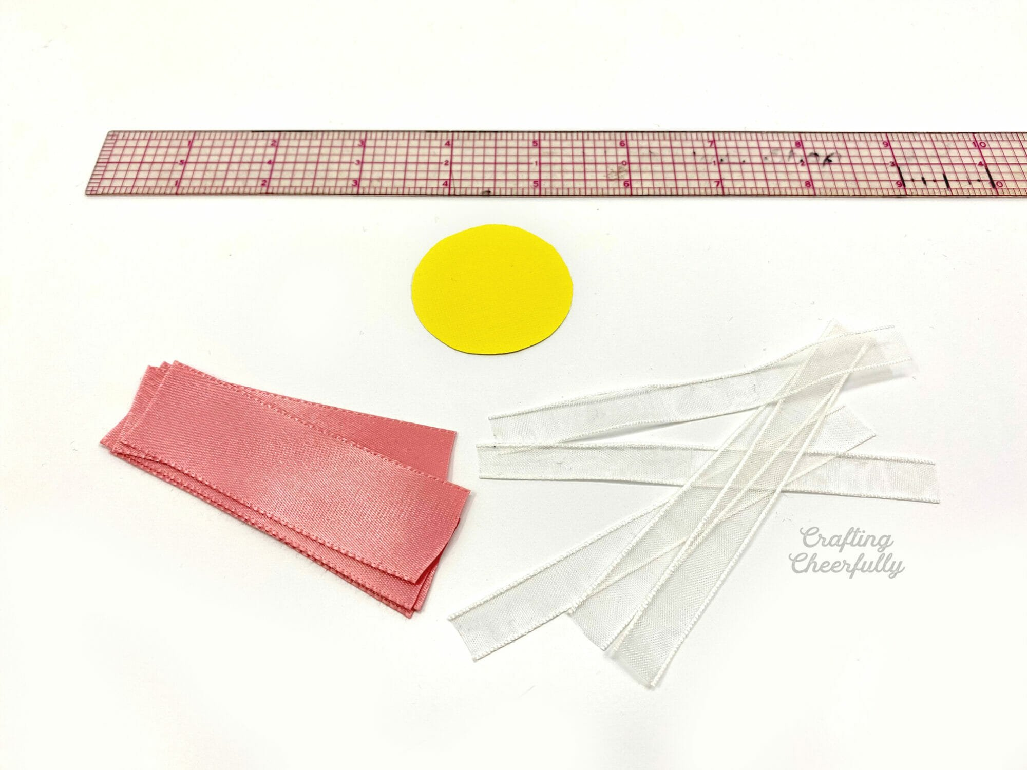 Ruler, ribbon and a paper circle lay on a table.