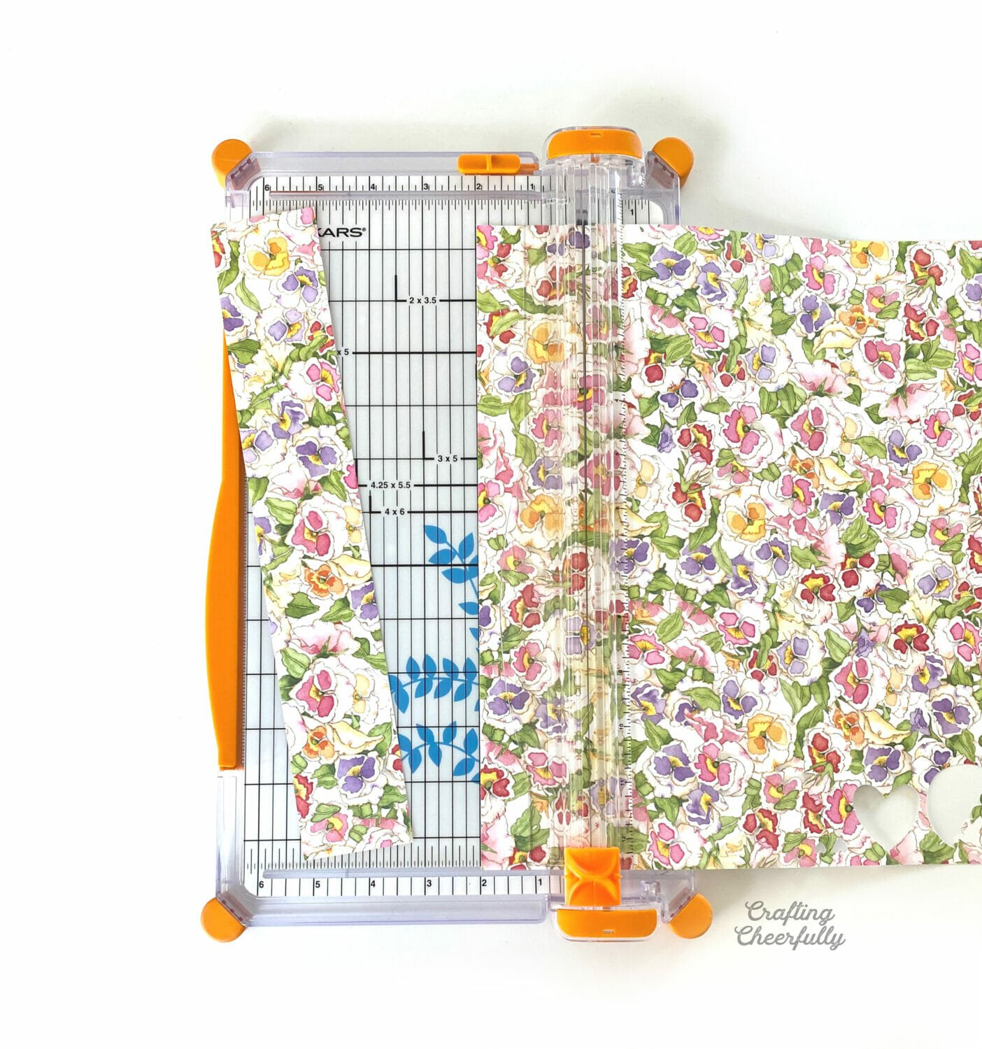 A paper trimmer trims floral paper into strips.