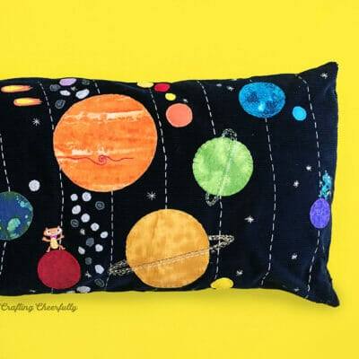 Solar system pillow featuring planets and stars laying against a yellow background.