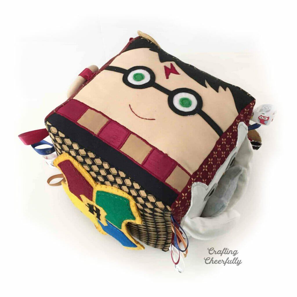 Harry Potter fabric activity cube with Harry Potter's face on top.