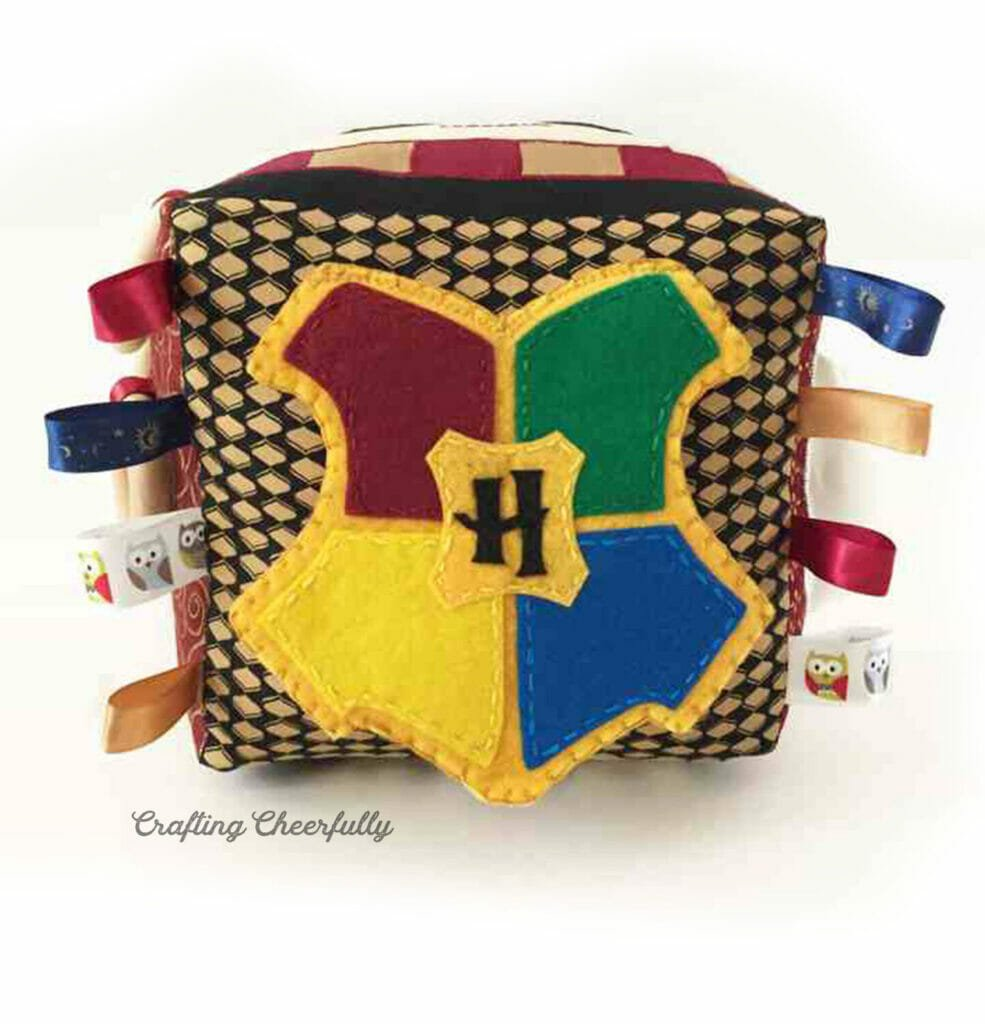 Side of the activity cube with a felt crest of Hogwarts.