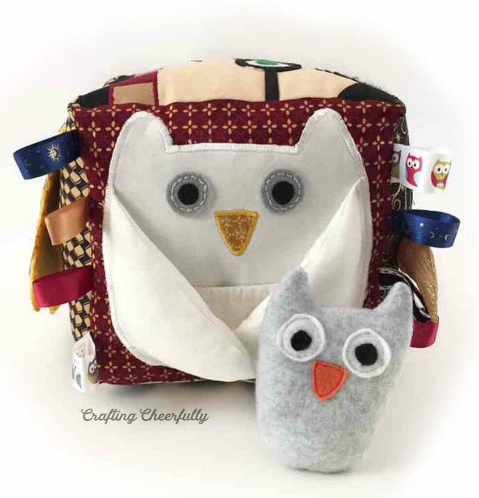 Side of the activity cube showing a white snowy owl and a gray baby fleece owl.