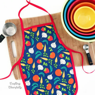 Colorful child's apron with veggie fabric lays on a cutting board next to primary colored bowls.