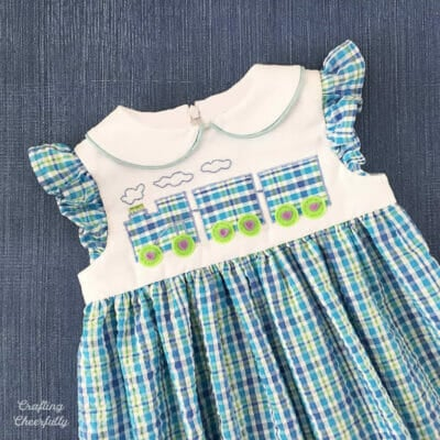 Blue plaid toddler dress with a train applique on the front.