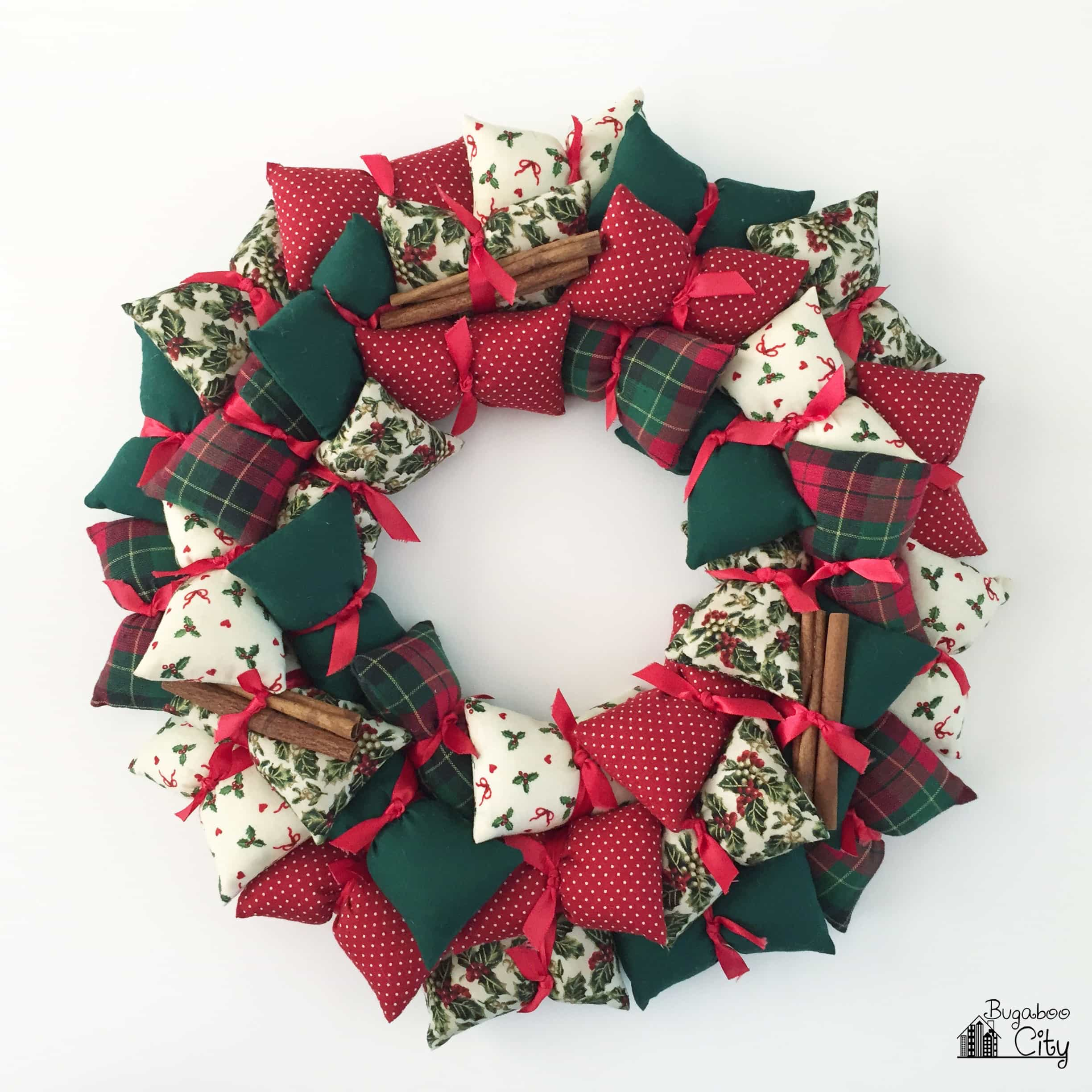 Pillow wreath made with red, white and green fabrics on a white background.