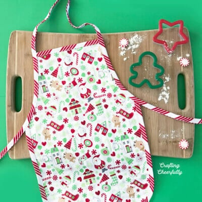 Red and green little kids apron laying on a cutting board next to red and green cookie cutters.