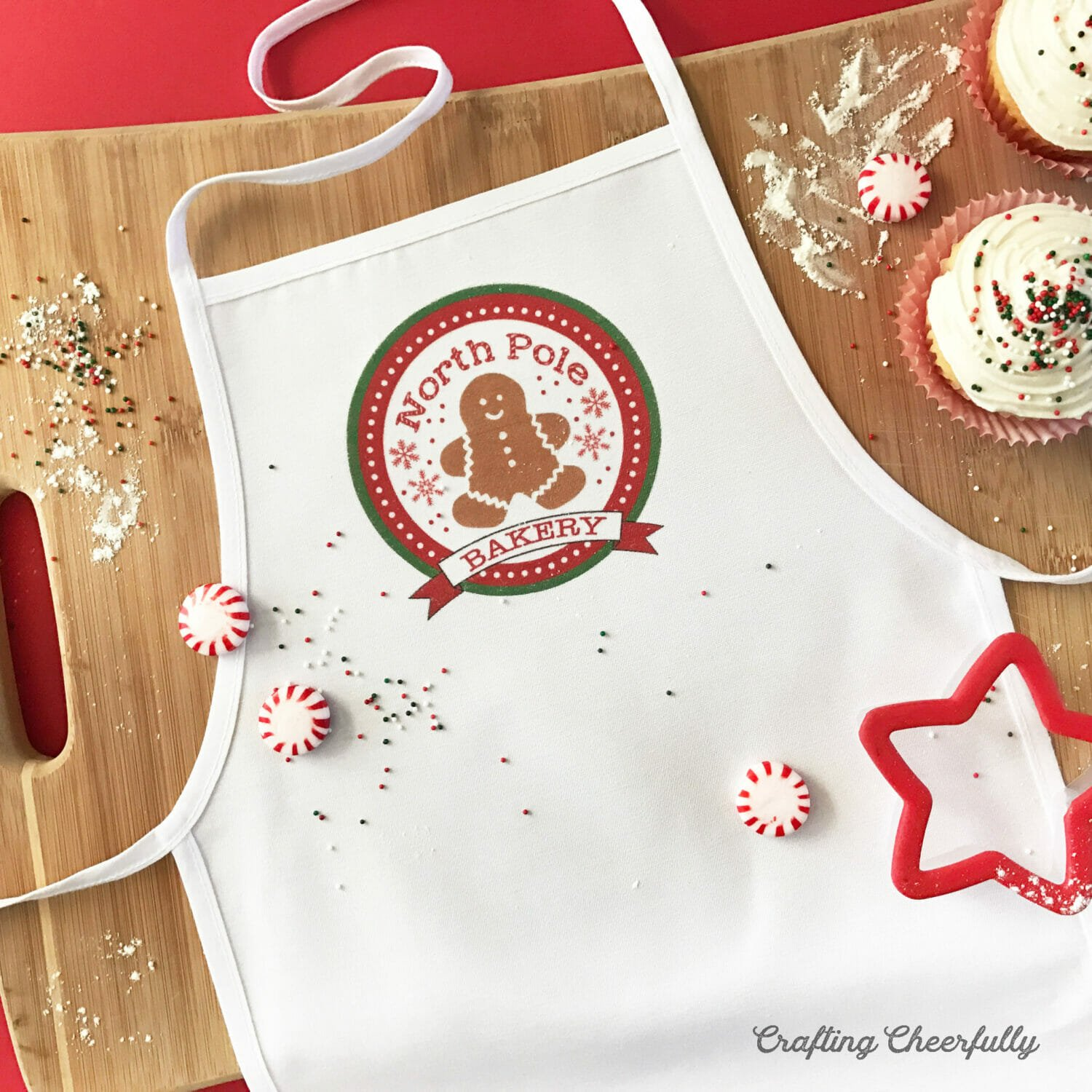 """White holiday apron with cute gingerbread image that says """"North Pole Bakery"""" lays on a cutting board with peppermints and cookie cutters."""