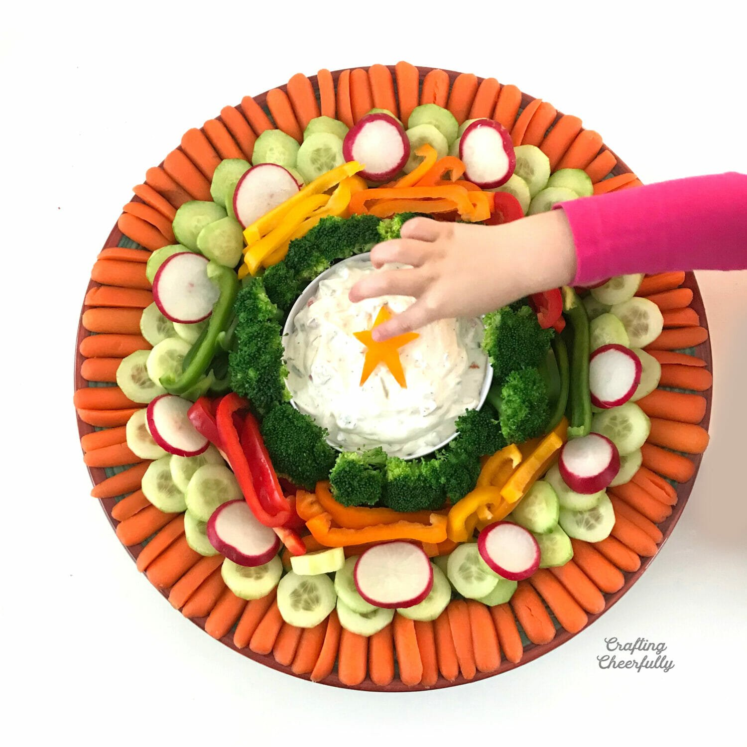 Holiday vegetable platter with a star in the center of the dip and a little girl pushing it in.