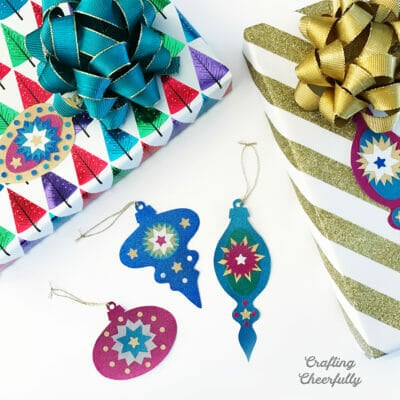 Sparkly and colorful gift tags lay next to colorfully wrapped gifts.