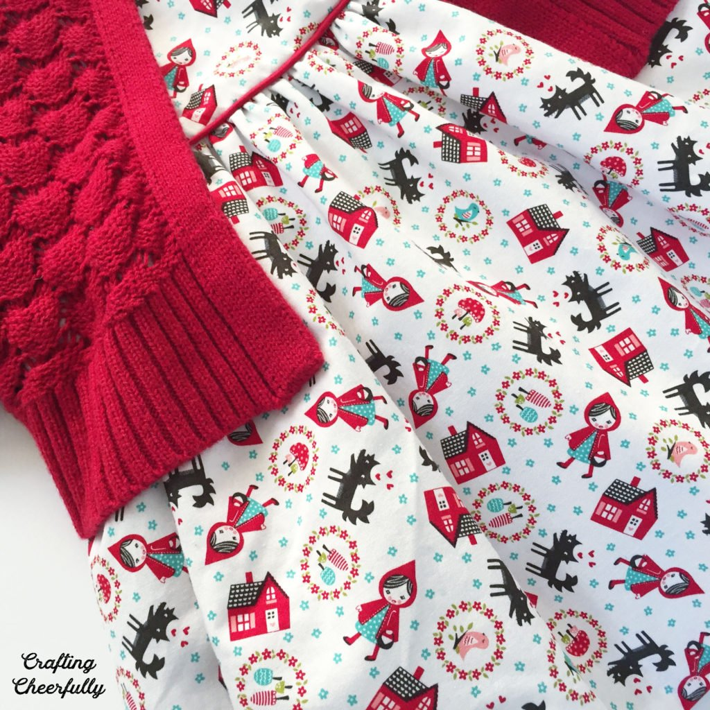 Close up of Little Red Riding Hood baby dress with red cape.
